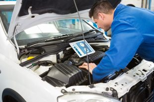 Mechanic using tablet to fix car